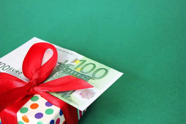 Банкнота 100 евро на подарочной коробке с красным бантом. зеленый фон. концепция праздника и денежных подарков.