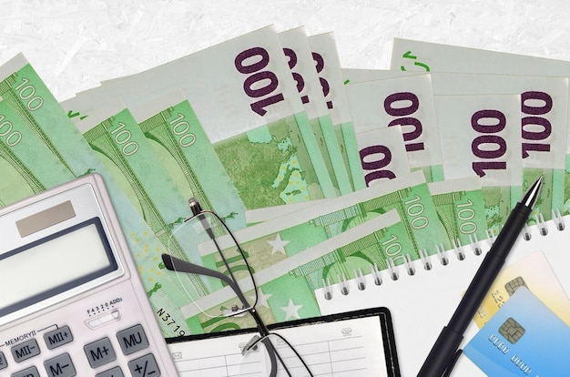100ユーロ紙幣と眼鏡とペン付きの電卓。納税シーズンのコンセプトまたは投資ソリューション。フィナンシャルプランニングまたは会計士の事務処理