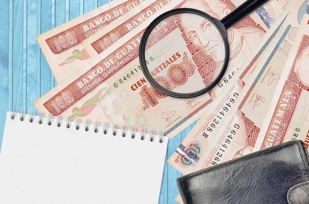100のグアテマラケツァール紙幣と黒い財布とメモ帳付きの虫眼鏡