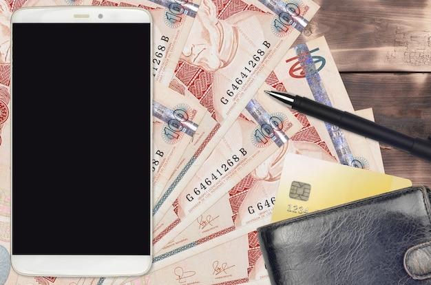 과테말라 케찰 지폐 100 개와 지갑과 신용 카드가있는 스마트 폰