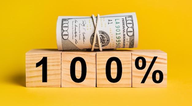 黄色い表面にお金で100の利息。ビジネス、金融、貯蓄、投資、税金の概念
