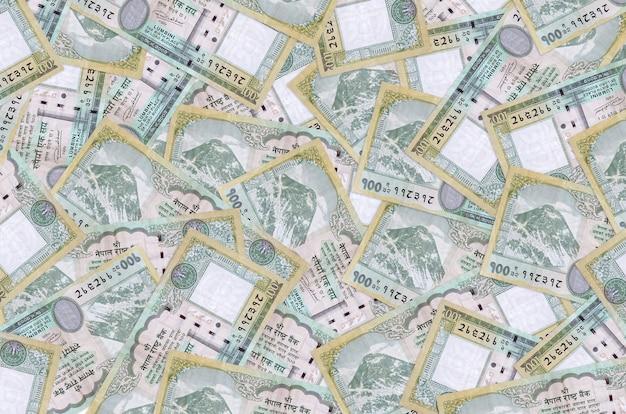 100ネパールルピーの請求書は大きな山にあります。豊かな生活の概念的な壁。巨額