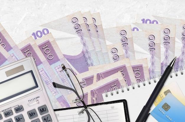 100フィリピンピソ紙幣とメガネとペン付き電卓