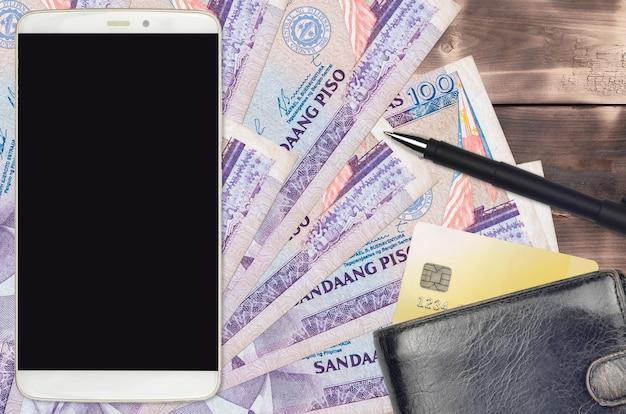100フィリピンペソの請求書と財布とクレジットカード付きのスマートフォン