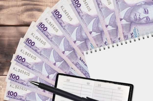 100 philippine piso bills fan and notepad with contact book and black pen. concept of financial planning and business strategy. accounting and investment