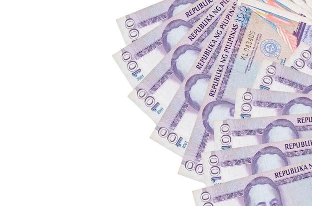100フィリピンペソの請求書は、コピースペースのある白い壁に隔離されています。豊かな生活の概念的な壁。大量の自国通貨資産