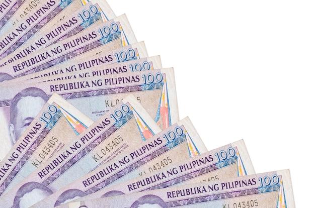 100フィリピンペソの請求書は、ファンのクローズアップに積み重ねられたコピースペースで白い壁に隔離されています。給料日の時間の概念または財務業務