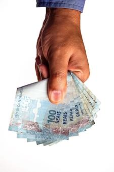 Банкноты 100 реалов бразилии, удерживаемые мужской рукой на изолированной белой поверхности.