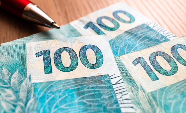 100 reais brazilian real banknotes on wooden surface in macro photography