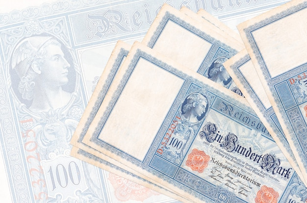 100 reich marks bills lies in stack on wall of big semi-transparent banknote. abstract presentation of national currency. business concept