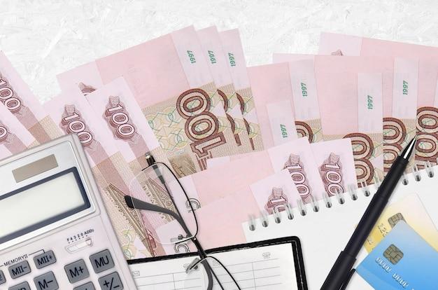 Купюры 100 российских рублей и калькулятор с очками и ручкой