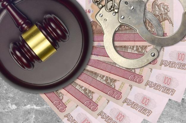 Купюры 100 российских рублей и судья молотком с полицейскими наручниками на столе суда. понятие судебного разбирательства или взяточничества. уклонение от уплаты налогов или уклонение от уплаты налогов