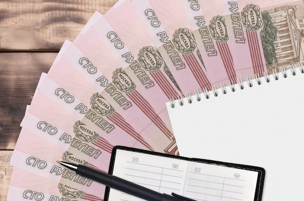 100 russian rubles bills fan and notepad with contact book and black pen. concept of financial planning and business strategy. accounting and investment