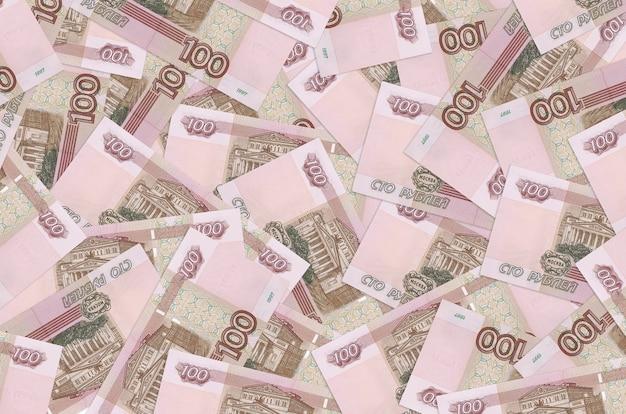 Купюры 100 российских рублей лежат в большой стопке