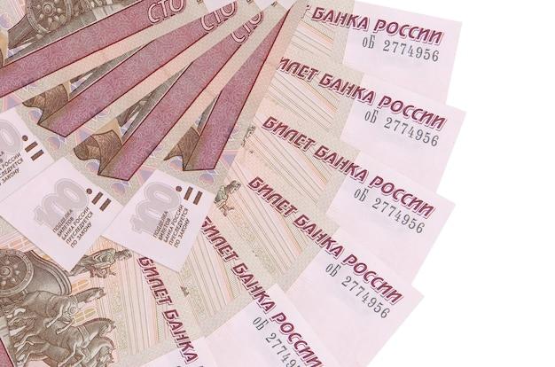 Банкноты 100 российских рублей лежат, изолированные на белой стене с копией пространства, сложены в форме вентилятора крупным планом. концепция финансовых операций