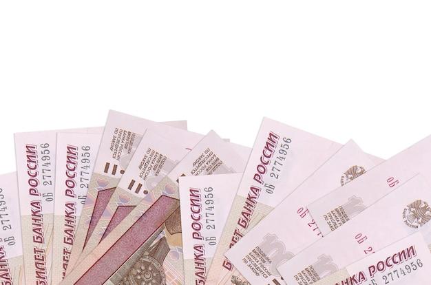 Купюры 100 российских рублей лежат на нижней стороне экрана, изолированного на белой стене с копией пространства.