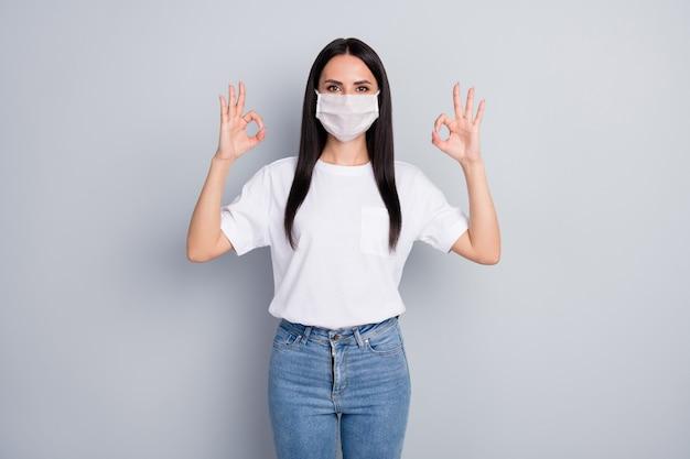 100安全コロナウイルス予防。自信を持って女の子の医療プロモーターは、医療マスクが抗菌保護を承認し、灰色の背景の上に分離された大丈夫なサイン着用スタイルの衣装を示しています