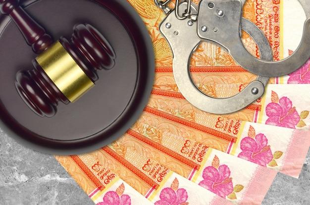 Купюры в 100 шри-ланкийских рупий и молоток судьи с полицейскими наручниками на столе в суде. понятие судебного разбирательства или взяточничества. уклонение от уплаты налогов или уклонение от уплаты налогов