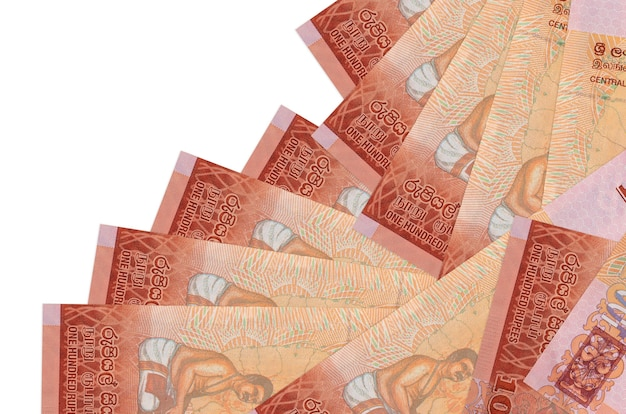 100 sri lankan rupees bills lies in different order isolated on white. local banking or money making concept.
