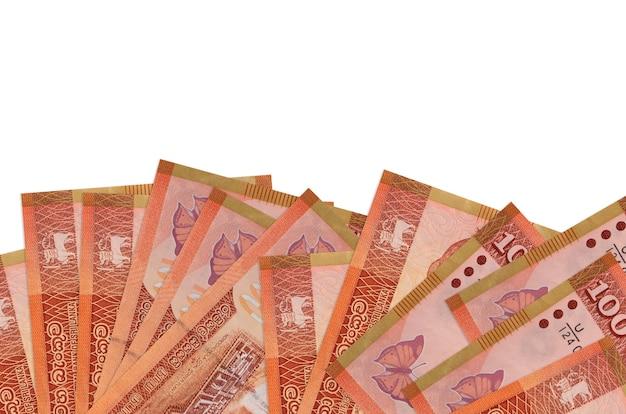 100 스리랑카 루피 지폐 복사 공간 흰 벽에 고립 된 화면의 아래쪽에 놓여 있습니다.