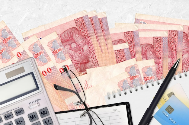 Купюры 100 тайских батов и калькулятор с очками и ручкой. концепция уплаты налогов или инвестиционные решения. финансовое планирование или бухгалтерские документы