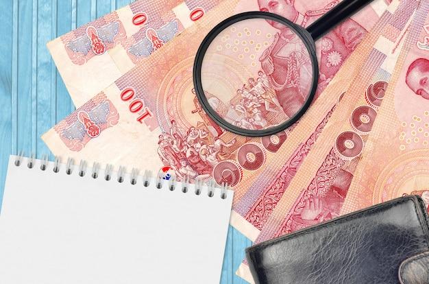 Банкноты 100 тайских батов и увеличительное стекло с черным кошельком и блокнотом. понятие о поддельных деньгах. поиск различий в деталях денежных купюр для обнаружения фальшивых денег