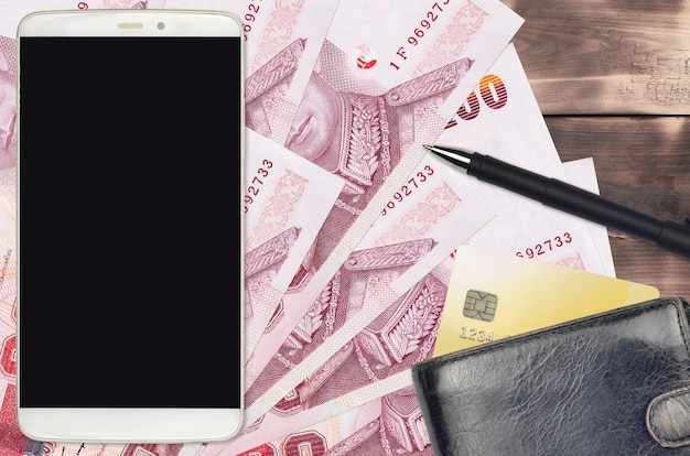 100バーツの紙幣と財布とクレジットカード付きのスマートフォン。