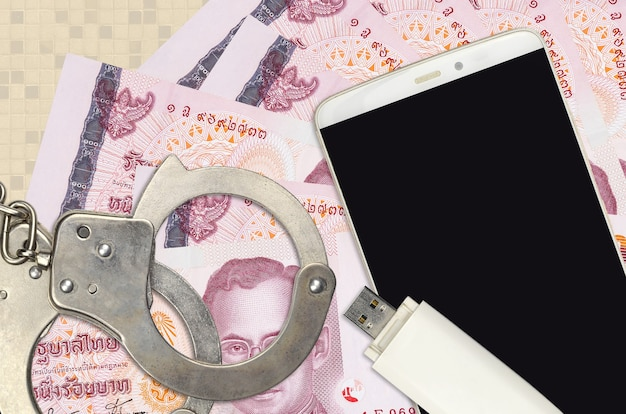 100 thai baht bills and smartphone with police handcuffs.