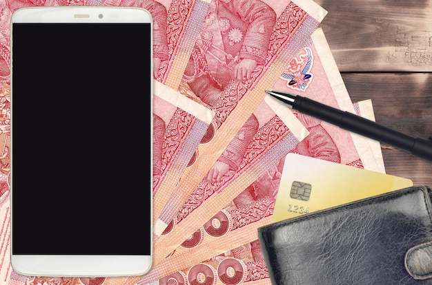 100 thai baht bills and smartphone with purse and credit card. e-payments or e-commerce concept. online shopping and business with portable devices usage