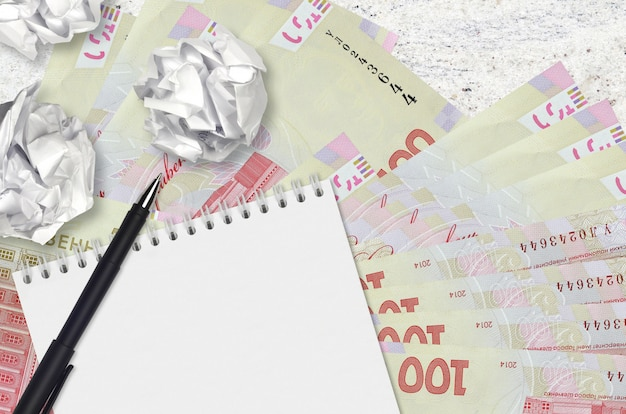 100ウクライナグリブナの手形と空白のメモ帳でしわくちゃの紙のボール。悪いアイデア以下のインスピレーションのコンセプト。投資のアイデアを探す
