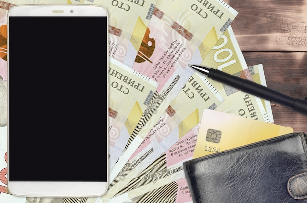 100ウクライナグリブナの紙幣と財布とクレジットカード付きのスマートフォン。