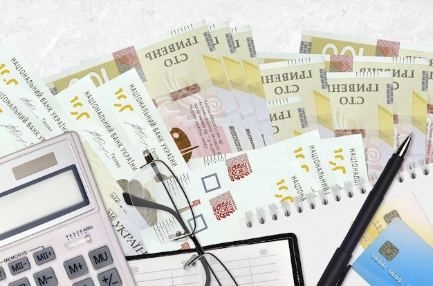 100 ukrainian hryvnias bills and calculator with glasses and pen. tax payment season concept or investment solutions.