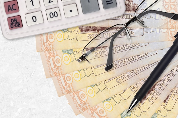 100 ukrainian hryvnias bills fan and calculator with glasses and pen. business loan or tax payment season concept. financial planning