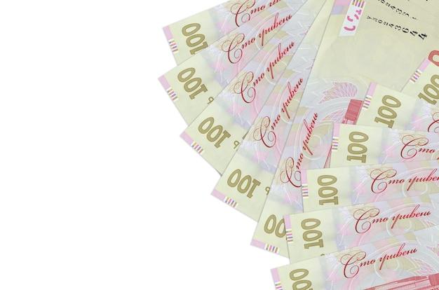 100のウクライナグリブナ紙幣はコピースペースのある白い壁に隔離されています。豊かな生活の概念的な壁。大量の自国通貨の富