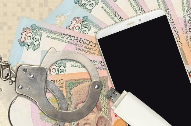 100 ukrainian hryvnias bills and smartphone with police handcuffs