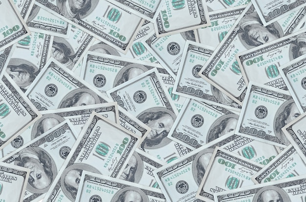 Купюры 100 долларов сша лежат в большой стопке