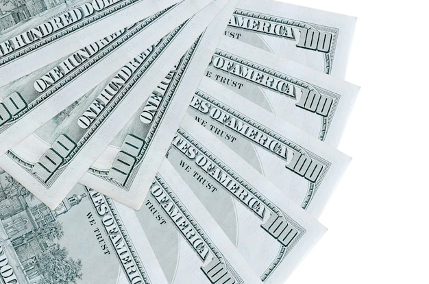 100 us dollars bills lies isolated on white background with copy space stacked in fan shape close up