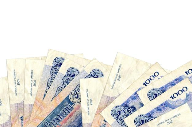 1000 캄보디아 리엘 지폐 복사 공간이 흰 벽에 고립 된 화면의 아래쪽에 놓여 있습니다.