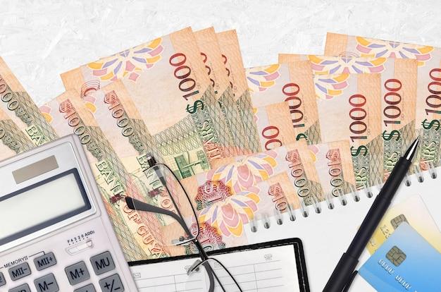 Купюры 1000 гайанских долларов и калькулятор с очками и ручкой.