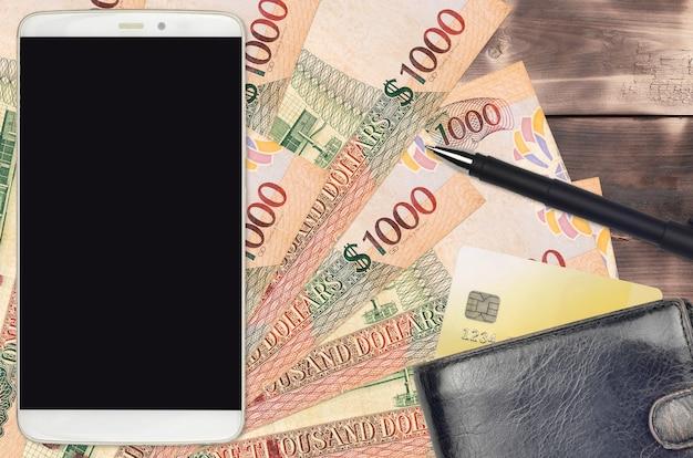 1000 가이아나 달러 지폐와 지갑과 신용 카드가있는 스마트 폰