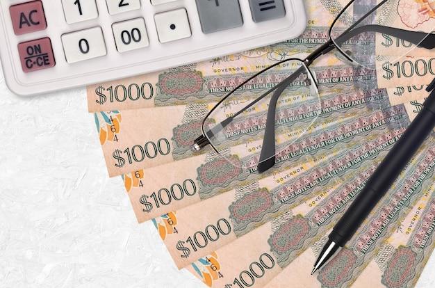 1000 가이아나 달러 지폐 팬과 계산기 안경과