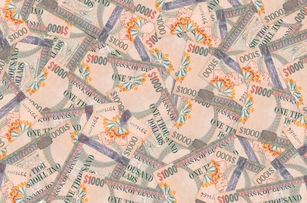 1000 가이아나 달러 지폐는 큰 더미에 놓여 있습니다.