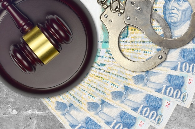 Купюры в 1000 венгерских форинтов и молоток судьи с полицейскими наручниками на столе в суде. понятие судебного разбирательства или взяточничества. уклонение от уплаты налогов или уклонение от уплаты налогов