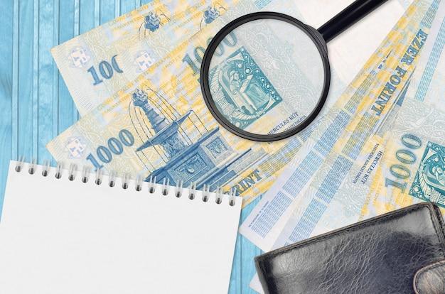 Банкноты 1000 венгерских форинтов и увеличительное стекло с черным кошельком и блокнотом.