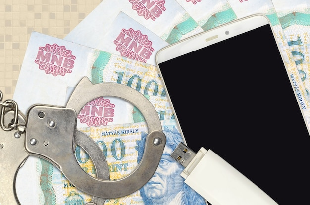 1000 hungarian forint bills and smartphone with police handcuffs