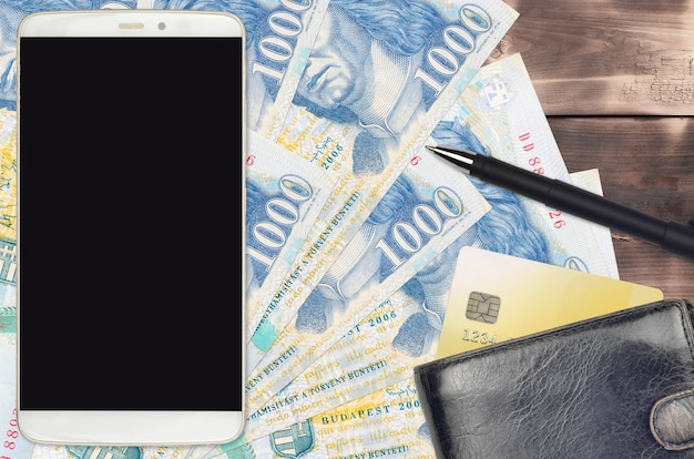 1000 hungarian forint bills and smartphone with purse and credit card