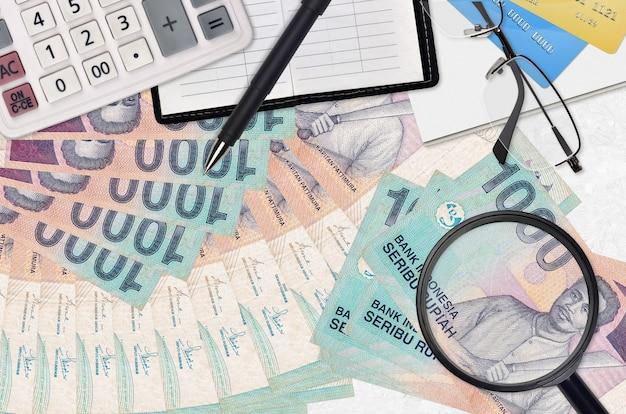 Банкноты 1000 индонезийских рупий и калькулятор с очками и ручкой.