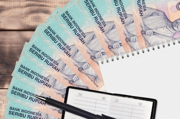 1000 indonesian rupiah bills fan and notepad with contact book and black pen. concept of financial planning and business strategy