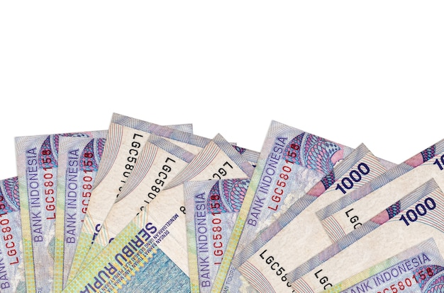 1000 indonesian rupiah bills lies on bottom side of screen isolated on white background with copy space
