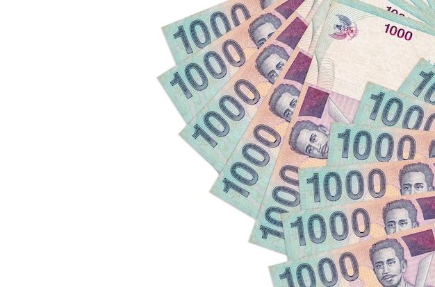 Банкноты 1000 индонезийских рупий лежат на белом фоне с копией пространства
